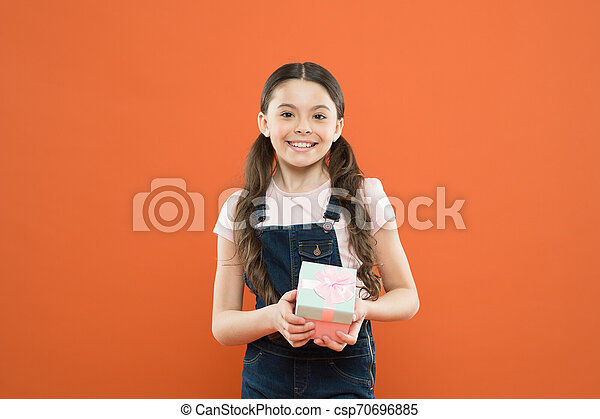 I was given such a great gift. Cute little girl holding gift box on orange background. Small child with gift pack on boxing day. Adorable kid with beautifully wrapped birthday gift box - csp70696885