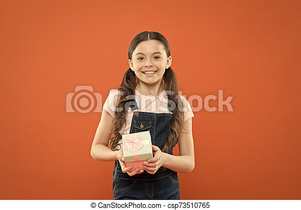 I was given such a great gift. Cute little girl holding gift box on orange background. Small child with gift pack on boxing day. Adorable kid with beautifully wrapped birthday gift box - csp73510765