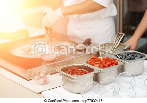 Ice cream kiosk at fair. Trays of blueberry, strawberry and raspberry - csp77932118