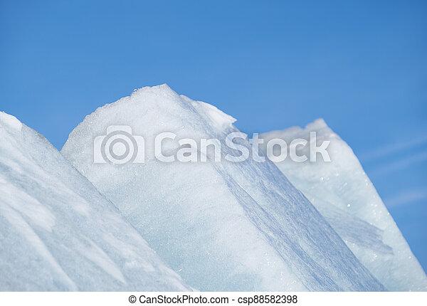 Ice pyramids on blue sky background. - csp88582398