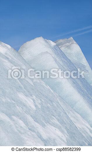 Ice pyramids on blue sky background. - csp88582399