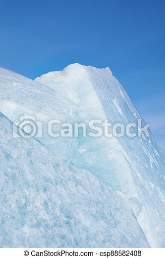 Ice pyramids on blue sky background. - csp88582408