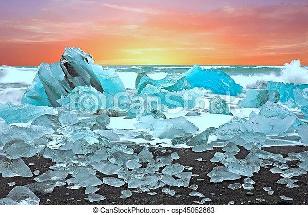 Ice rocks on a black sand beach at Jokulsarlon in Iceland at twilight - csp45052863