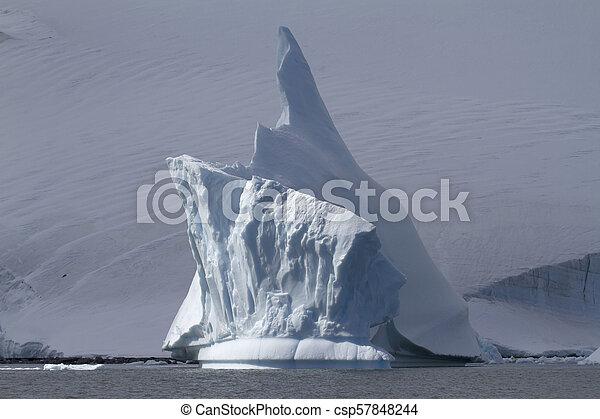 iceberg with a high arrow top near the Antarctic coast on a cloudy day - csp57848244