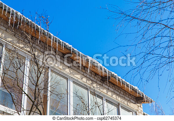 Icicles hanging from the roof. Winter in town. - csp62745374