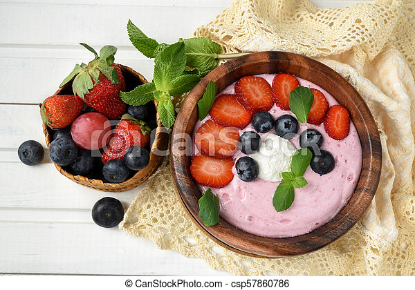 Ideas for healthy summer breakfast op dessert. Smoothies in bowls with strawberry, blueberry berry. With oatmeal, fresh berries. - csp57860786
