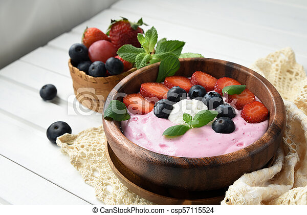 Ideas for healthy summer breakfast op dessert. Smoothies in bowls with strawberry, blueberry berry. With oatmeal, fresh berries. - csp57115524