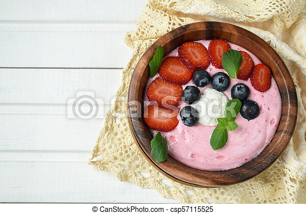 Ideas for healthy summer breakfast op dessert. Smoothies in bowls with strawberry, blueberry berry. With oatmeal, fresh berries. - csp57115525