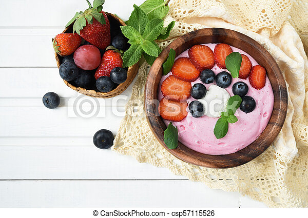 Ideas for healthy summer breakfast op dessert. Smoothies in bowls with strawberry, blueberry berry. With oatmeal, fresh berries. - csp57115526