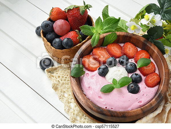 Ideas for healthy summer breakfast op dessert. Smoothies in bowls with strawberry, blueberry berry. With oatmeal, fresh berries. - csp57115527