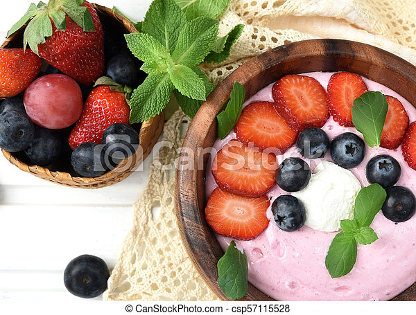 Ideas for healthy summer breakfast op dessert. Smoothies in bowls with strawberry, blueberry berry. With oatmeal, fresh berries. - csp57115528