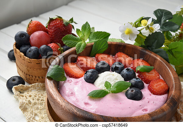 Ideas for healthy summer breakfast op dessert. Smoothies in bowls with strawberry, blueberry berry. With oatmeal, fresh berries. - csp57418649