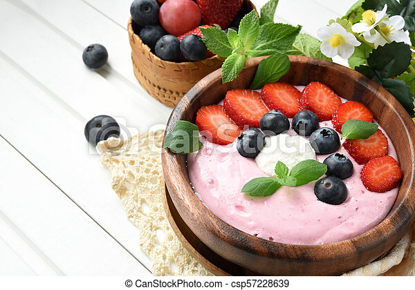 Ideas for healthy summer breakfast op dessert. Smoothies in bowls with strawberry, blueberry berry. With oatmeal, fresh berries. - csp57228639
