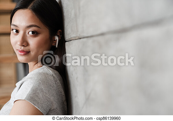 Image of asian woman using earphones while leaning on concrete wall - csp86139960