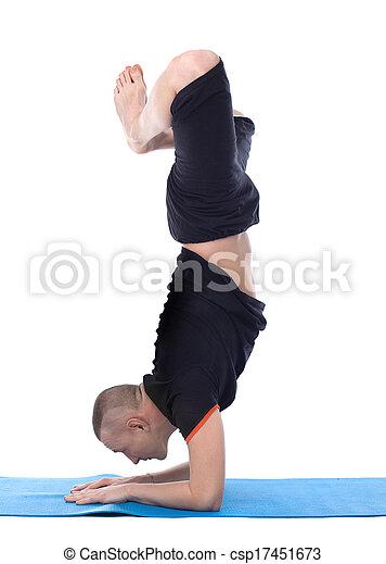 image of calm man doing yoga handstand in studio