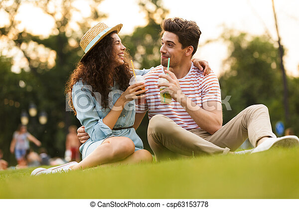 Image of caucasian couple man and woman 20s sitting on green grass in park, and drinking beverages from plastic cups - csp63153778