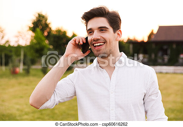 Image of caucasian happy man 25-30 wearing white shirt smiling, and talking on black smartphone while walking outdoor on nature - csp60616262