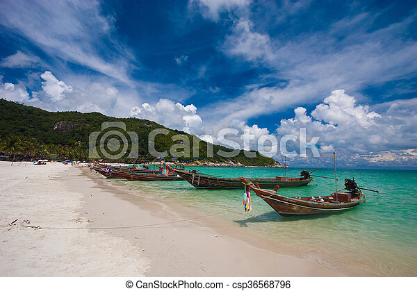 Image of empty long tail boat on tropical beach. Clear water and blue sky with clouds. Horizontal - csp36568796