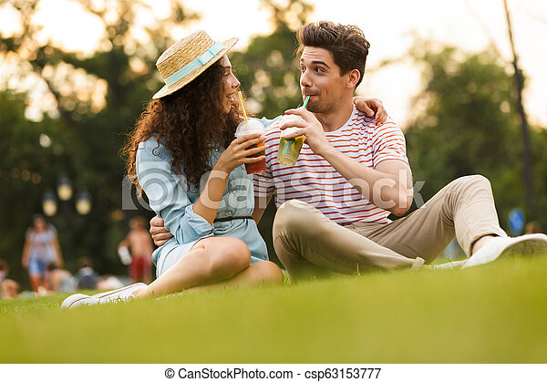 Image of european couple man and woman 20s sitting on green grass in park, and drinking beverages from plastic cups - csp63153777