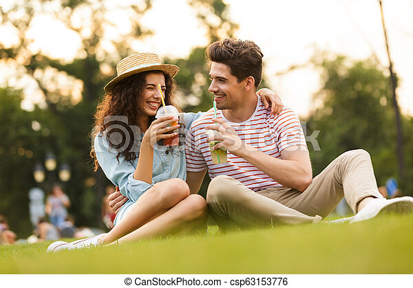 Image of happy couple man and woman 20s sitting on green grass in park, and drinking beverages from plastic cups - csp63153776