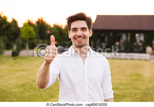Image of happy young man 25-30 wearing white shirt smiling, and showing thumb up while walking outdoor on nature - csp60616255