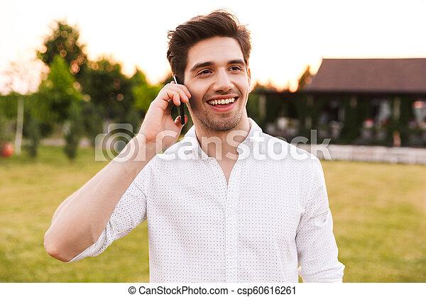 Image of joyful young man 25-30 wearing white shirt smiling, and talking on black mobile phone while walking outdoor on nature - csp60616261