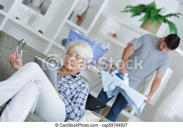 image of senior female sitting on sofa with laptop - csp59744937
