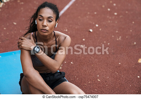 Image of young african american woman sitting at playground outdoors - csp75474007