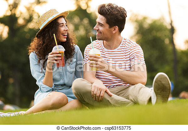 Image of young couple man and woman 20s sitting on green grass in park, and drinking beverages from plastic cups - csp63153775
