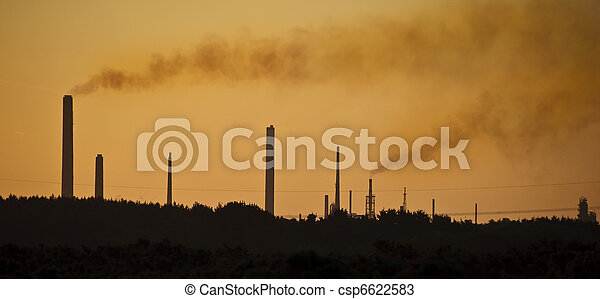Image with orange tint to highlight the impact of industrial chimney stacks polluting the air in a natural landscape setting - csp6622583