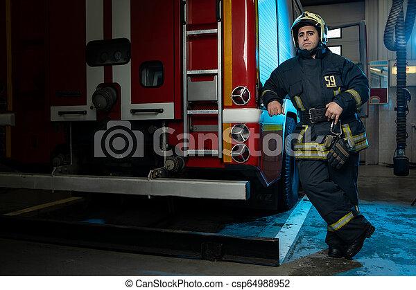 Una foto completa de un bombero en el camión de bomberos - csp64988952