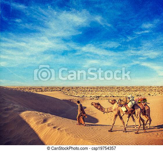 Una antigua imagen de viaje retro hipster de estilo Rajasthan de fondo de viaje - el cameleer de la India (conductor de camello) con camellos en dunas del desierto de Thar con una textura extenuada. Jaisalmer, Rajasthan, India - csp19754357
