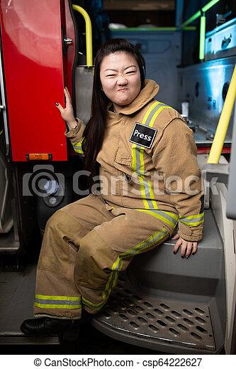 Una foto de una bombero en el fondo del camión de bomberos - csp64222627