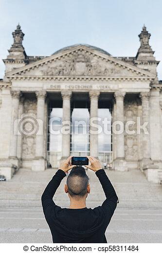 Un hombre tomando una foto del Reichstag, en Berlín - csp58311484