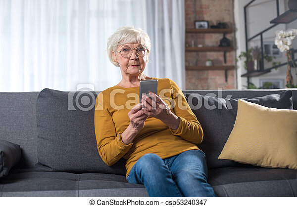 Impressed Old Lady Resting On Couch At Living Room With Phone