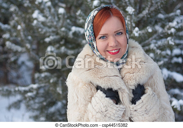 in a scarf on the background of the winter forest - csp44515382