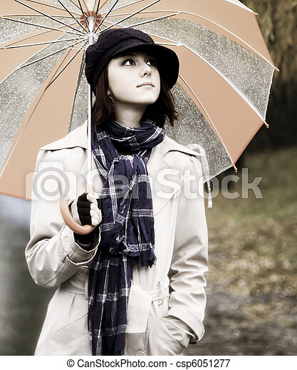 in cloak and scarf with umbrella at park in rainy day. Photo in vintage style with nature colour. - csp6051277