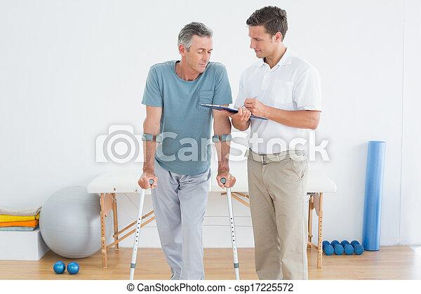 Terapeuta discutiendo informes con un paciente discapacitado - csp17225572