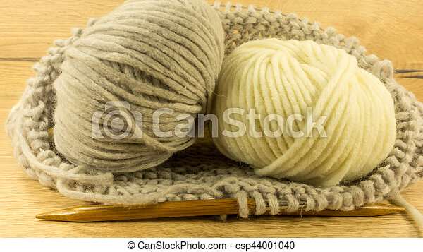 Incomplete knitting project with a woolen ball and wooden needles - csp44001040