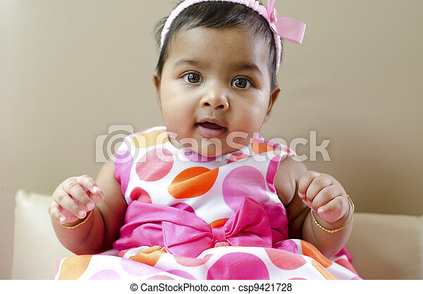 6dfaf37ba7 Adorable 6 months old indian baby girl sitting on sofa.