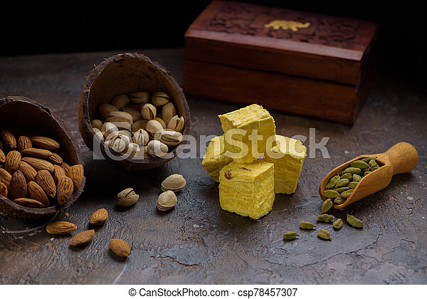 Indian dessert patisa, cardamom grains in wooden scoop, pistachios, almond and wooden box on concrete kitchen surface. - csp78457307