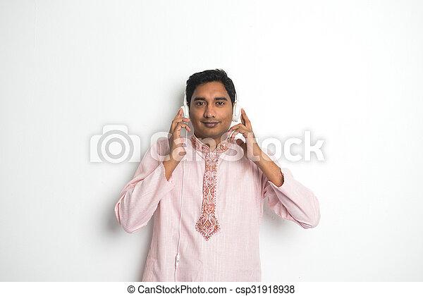 indian male enjoying music in traditional wear