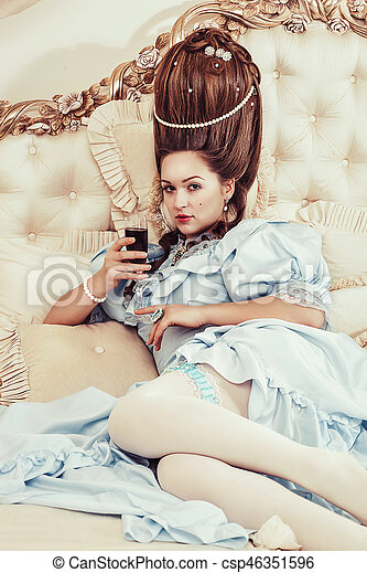 Indoors shot in the Marie Antoinette style. A young sexy girl in a lush blue retro dress with a high hairstyle lies on the bed with a glass of sparkling wine in her hand. Woman tired of luxury - csp46351596