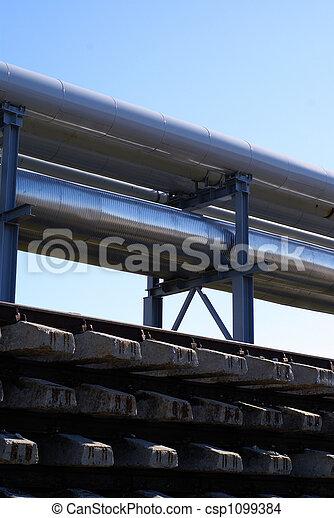 industrial pipelines on pipe-bridge against blue sky - csp1099384