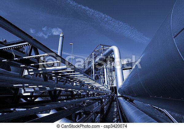 industrial pipelines on pipe-bridge against sky in blue tone          - csp3420074