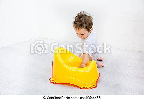 Infant child baby boy toddler play with potty toilet stool pot on a white background - csp40544465