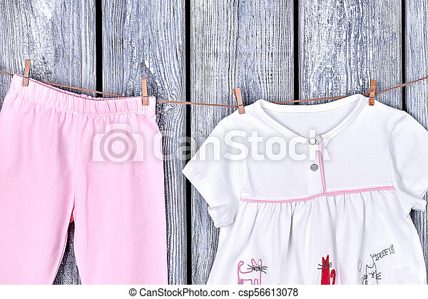 04d289e20259 Infant girl clothing on rope. toddler girl top and pants hanging on  clothesline on grey wooden background.