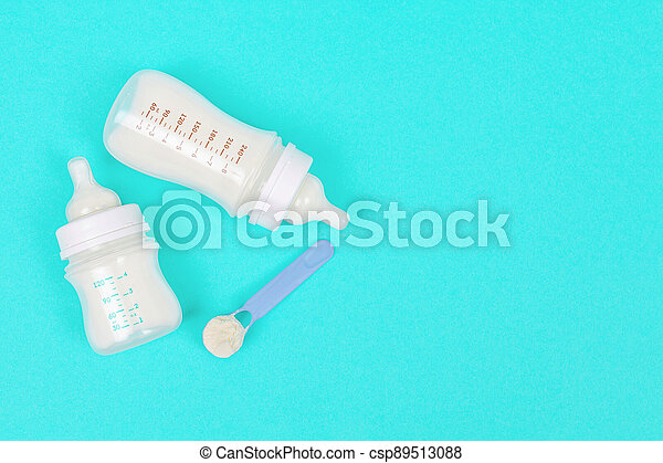 Infant milk in baby bottles on a mint green background - csp89513088