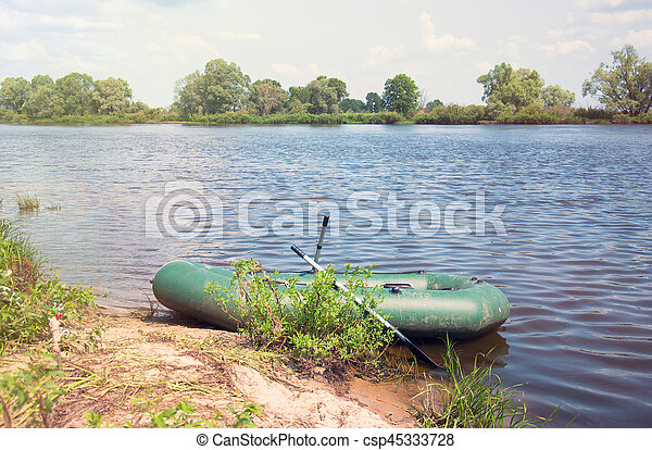 Inflatable boat on the a river near shore - csp45333728