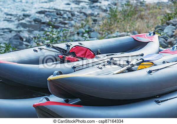Inflatable boats on the mountain river shore. - csp87164334